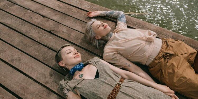 frauen-urlaub-lesbisches-paar-jung-attraktiv-tattoos-see-natur-glueckliche-beziehung-gruende-warum-es-sich-lohnt-lesbisch-zu-sein-lesbischer-humor-witze