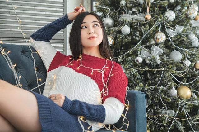 woman-with-string-lights-near-christmas-tree-weihnachtsgeschenke-frauen-lesben-nachdenken